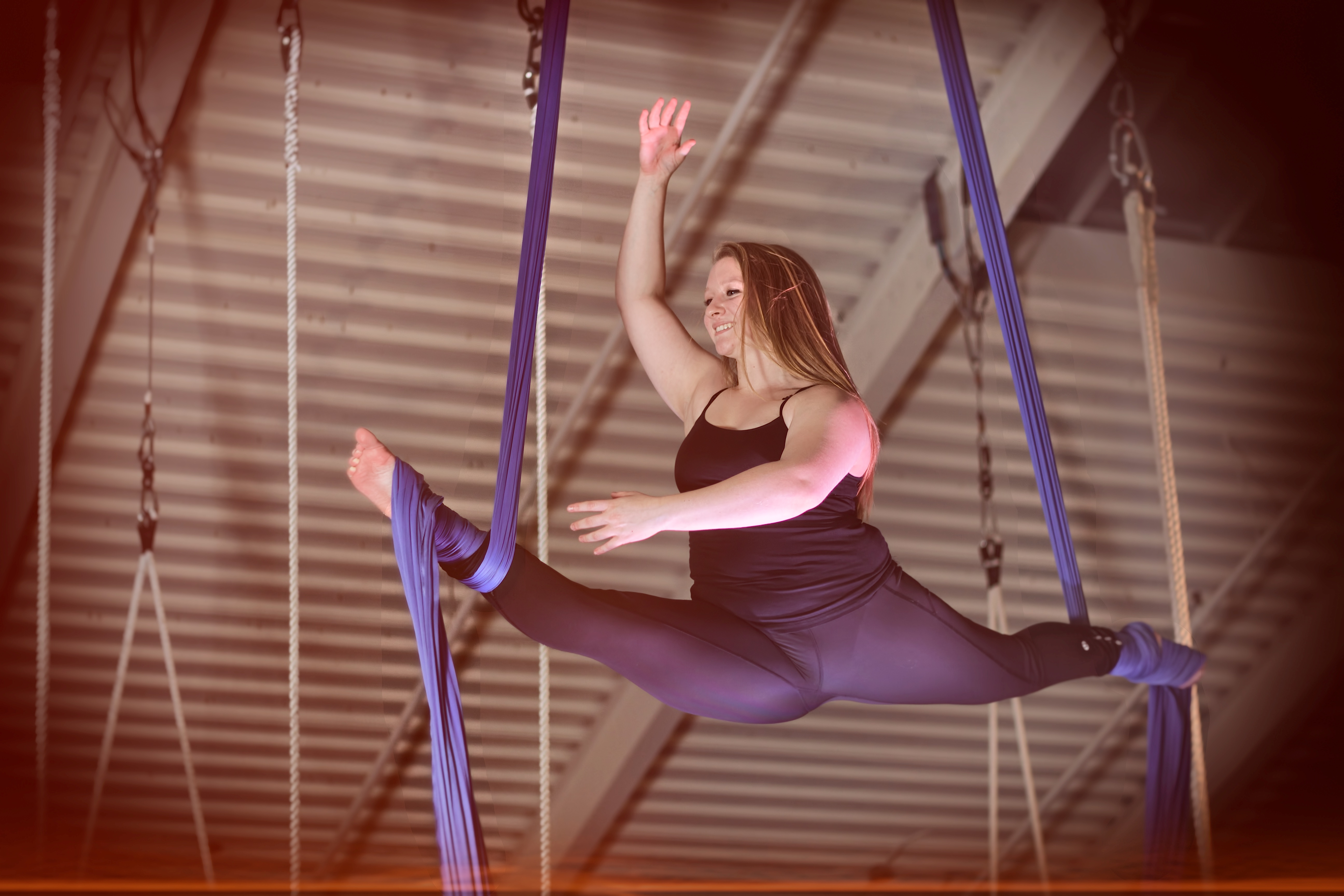 Sydney performing a split balance, with her legs wrapped around the silks and her arms in the air, balancing in the splits.
