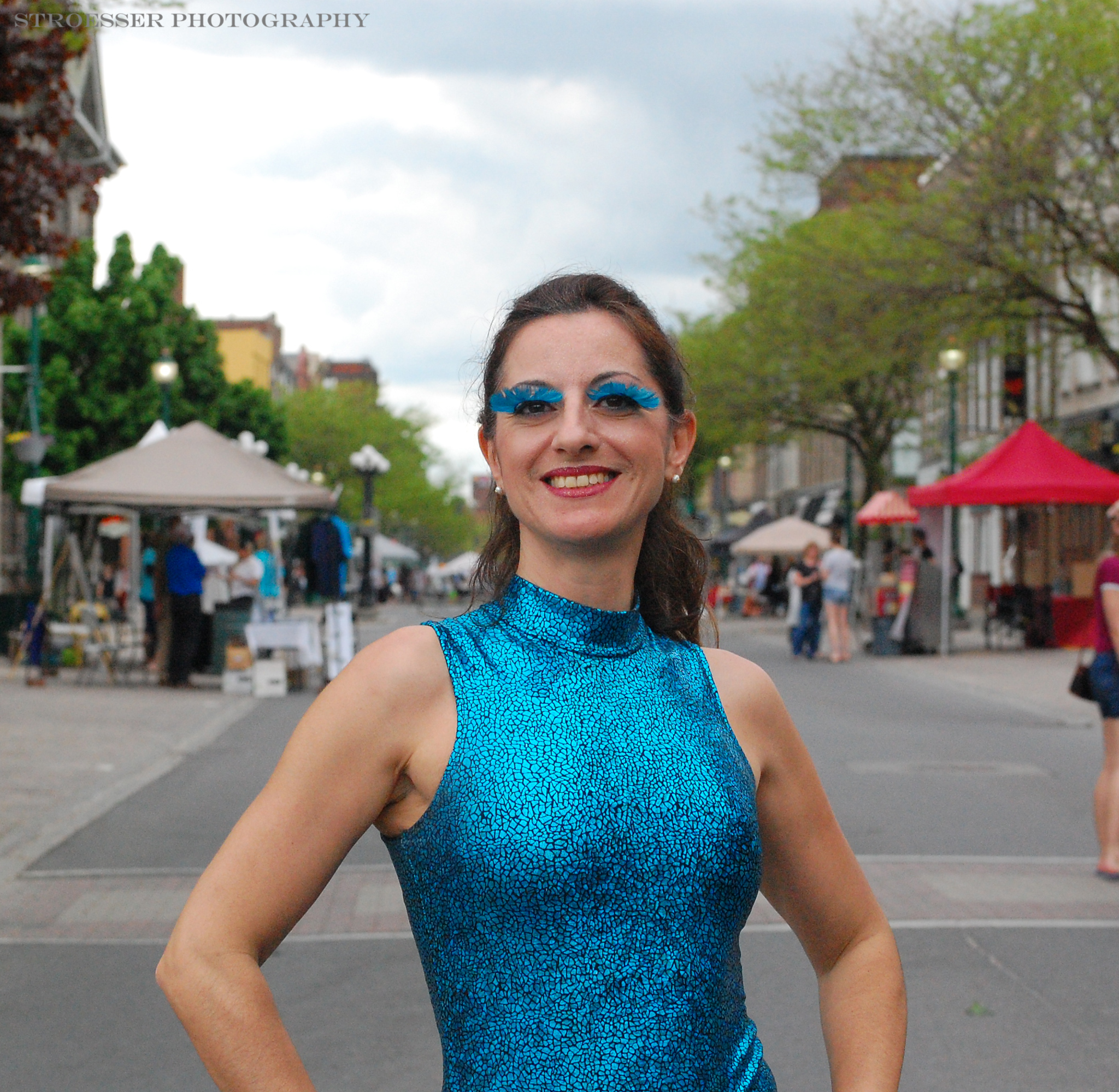 A photo of Olga from the waist up. She is wearing a teal sparkly bodysuit and matching feathery eyebrows. She has long dark hair that is pulled back and there is a street behind her with tents.